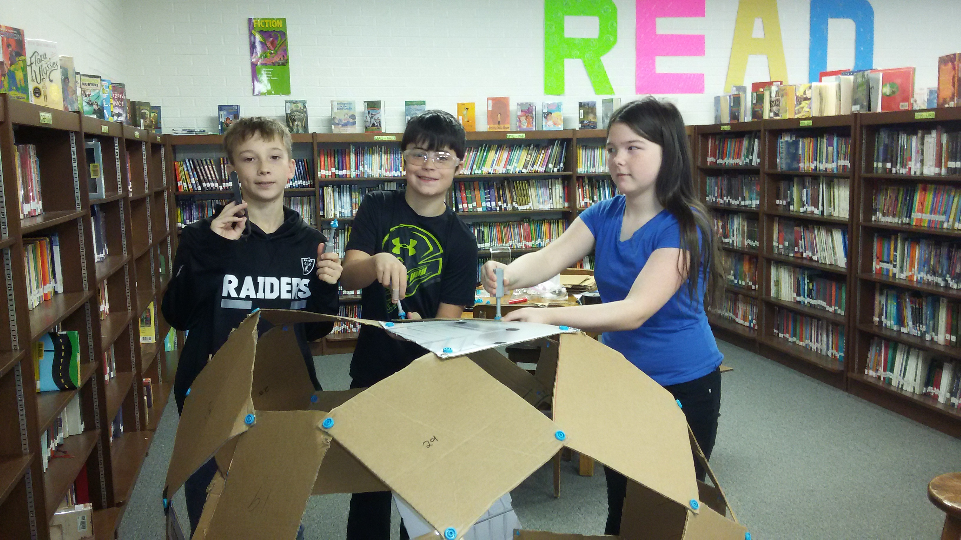 Middle school students in library working on a project
