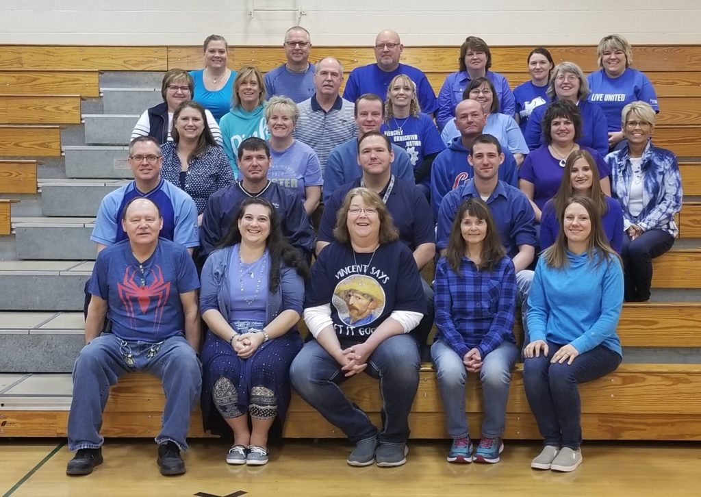 group photo of UMS staff wearing blue